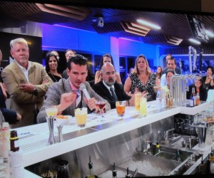 The judges critiquing cocktails under timed conditions, as Norwegian Cruises Lines' Wes Cort, standing, looks on.
