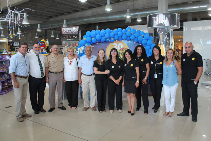 Neutral CEO Enrique Urioste, far left, and staff and guests, celebrate the border store's 30th anniversary in festivities in one of the stores in the town of Chuy.